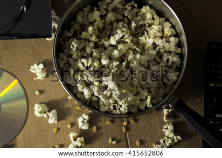 A Dramatic Anticipatory Shot of Freshly Popped Popcorn and a DVD in Preparation for a Great Movie Night