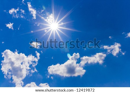 A dramatic blue sky with white clouds and sun