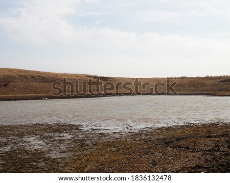 A dramatic landscape of a dry lake. Dry bottom of a dried-up lake in large cracks. Conceptually: Environmental Related Issues of Global Warming