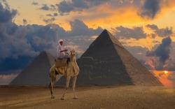 A dramatic morning sky over Giszeh in Upper Egypt. An Egyptian in blue robe with a turban sits on a camel in front of the pyramids at sunrise. There are exciting clouds in the sky.