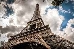 A dramatic perspective of the Eiffel Tower and a moody cloudscape behind it in Paris, France.