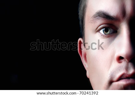 A dramatic portrait of a young man, isolated on black background. Half face