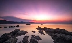 A dramatic scenic landscape shot of rocks in the ocean with beautiful sky in sunset Time. Shooting in long exposure mode and cold tone during summer time. Samui island, Thailand.