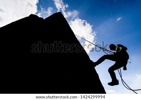 A dramatic silhouette of a climber rappeling down a rock wall. Rock climber with a rope abseil down. Mountaineer jumping down on climbing rope. Extreme adventure sport of rock climbing. Photo stock ©