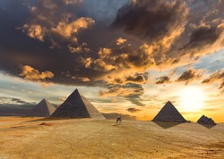 A dramatic sunrise with impressive clouds over the desert and pyramids at Giza in Egypt. A man in a turban is riding a camel. The sun casts long shadows.