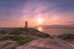 A dramatic sunset at Peggy's Cove Lighthouse Atlantic Coast Nova Scotia Canada. The most visited tourist location in the Atlantic Canada and famous Lighthouse captured with vibrant colors.