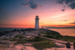 A dramatic sunset at Peggy's Cove Lighthouse Atlantic Coast Nova Scotia Canada. The most visited tourist location in the Atlantic Canada and famous Lighthouse captured with vibrant colors