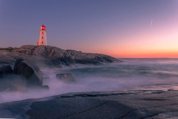 A dramatic sunset captured at the blue hour at Peggy's Cove Lighthouse Atlantic Coast Nova Scotia Canada as the ocean waves pound the rugged shore.