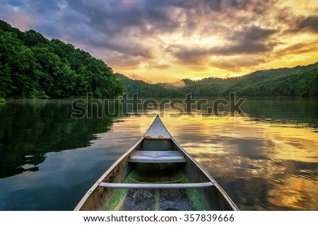 Stock Photo A dramatic sunset from an old canoe on a clam mountain lake in the Appalachian Mountains of Kentucky.
