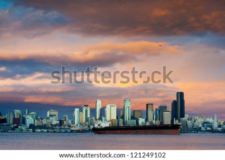 A dramatic sunset paints a beautiful sky over the Seattle, Washington skyline and Elliott Bay with a commercial ship in the foreground.