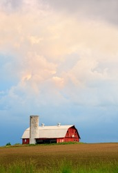 A dramatic sunset sky hangs over a red barn with silo and basketball hoop in the Midwestern United States.
