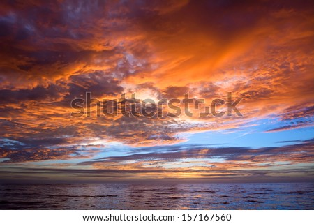 A dramatic, vibrant sunset over a calm ocean in Mexico
