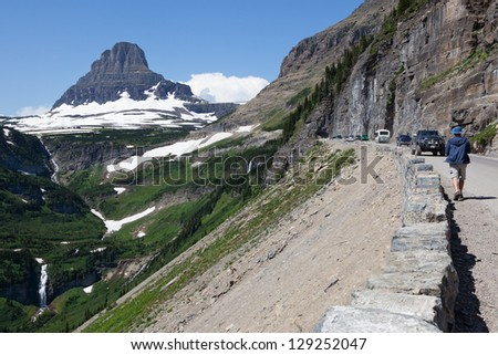 A dramatic view of Glacier National Park in Montana with Mt. Cannon in the background, lush greenery with waterfalls and a road loaded with tourists taking in the sights.