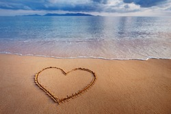 A drawing of a heart on a yellow sand at a beautiful seascape background.