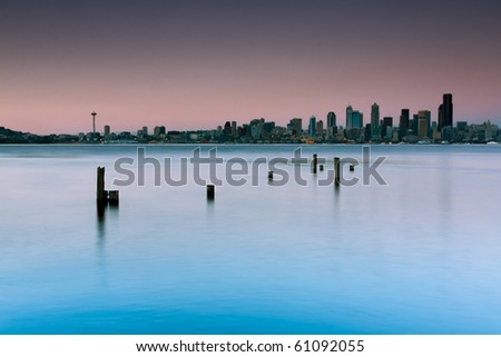 A dreamy look of a city skyline with skyscrapers shot from a beach with some old pier logs in the foreground. Long exposure creates a creamy water surface of waves and ripples.