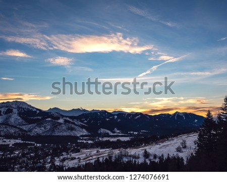 A dreamy sunset sky with dreamy clouds on it and the mountains on the horizon.