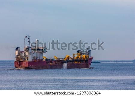 A Dredging Ship in Harbor with water flowing from pumps on deck
