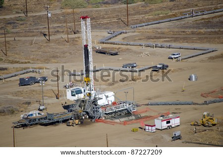 A drilling rig sets up on an existing oil lease