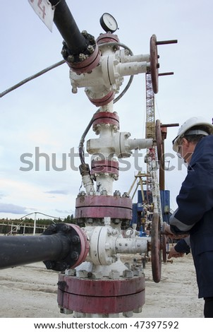 A drilling rig worker. Focus is on the instruments.