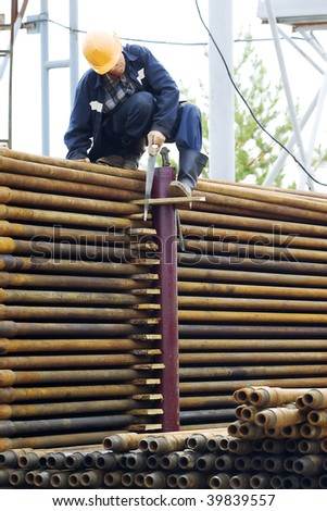 A drilling rig worker. Focus is on the pipes.