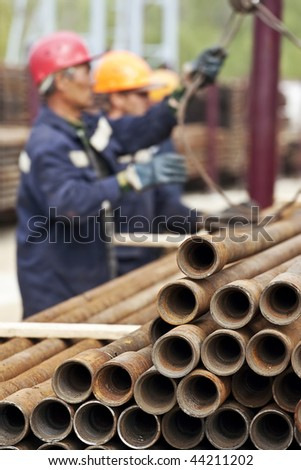 A drilling rig workers. Focus is on the pipes.