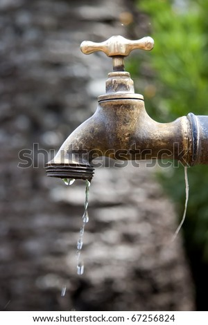 a dripping faucet bronze in exteriors - stock photo