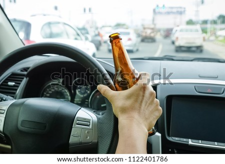 A driver holding alcoholic bottle while driving / Drunk driving concept #1122401786