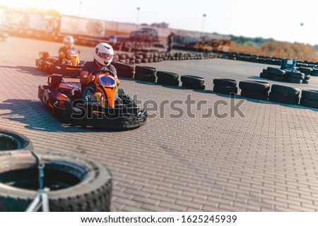 A driver in gear and helmet drives a racing car. In action. Go karts racing, sreet karting, rent. extreme sport. fun entertainment for drivers. Soft light glow, copy space Zdjęcia stock ©