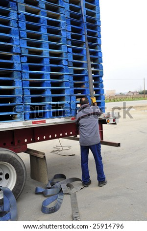 A driver unloads his cargo of wooden pallets delivered to a winery