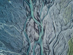 A drone shot from above on a green and blue metallic looking glacier river stream in Iceland with repeating grey, beige and dark green patterns, textures and structures running from top to down