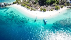 A drone shot of a paradise island with some boats anchored around in Komodo National Park, Flores, Indonesia. Green middle part of the island turns into white sand beach and further into turquoise sea