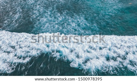 A drone shot of a surfer diving into the crashing waves in the middle of the Wakiki ocean in Honolulu, Hawaii #1500978395