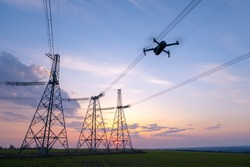A drone taking pictures of high-voltage power lines in the beautiful evening sky.