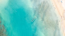 A drone view of an outrigger canoe floating in clear blue hawaiian waters in honolulu, Hawaii