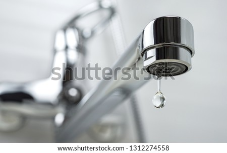 A drop of pure water dripping from the tap. Selective focus.