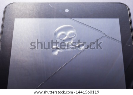 A drop of water in the form of a skull with a bone on a broken tablet PC with a cracked touchscreen glass. #1441560119