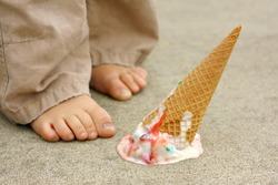 a dropped rainbow colored ice cream cone lays upside down on the sidewalk at the feet of a young child