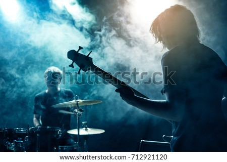 A drummer and bass guitarist. Rock concert. Scene. Smoke Stage light.