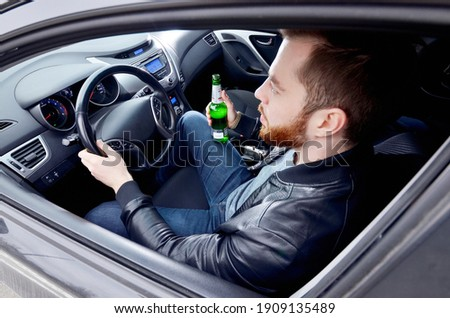 A drunken man driving a car with a bottle of alcohol in his hand.A man holds a driving wheel and a bottle of beer. Сток-фото ©