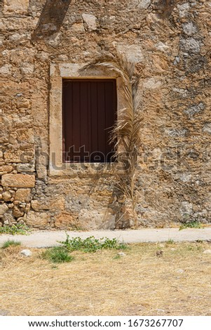 a dry, yellowed branch of a palm tree leans against the stone wall. the window is shuttered.