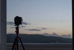 a dslr camera on a tripod is silhouetted against a sunset sky from a balcony as it takes a time-lapse set of pictures