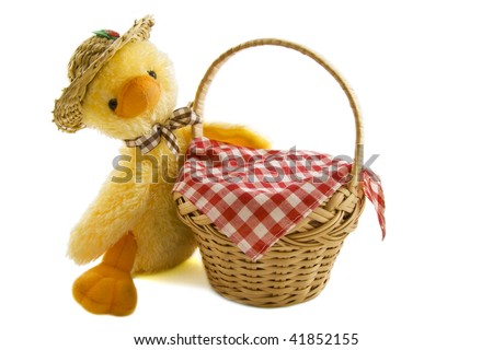 A duckling with funny hat behind a wooden basket isolated