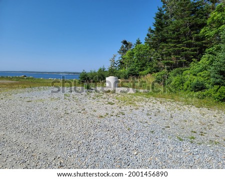A dug well near the edge of the wilderness and in front of the ocean in a scenic, Nova Scotian view. The path to the dug well is filled with gravel. Stock fotó ©