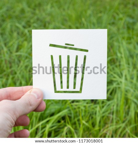 A dumpster icon, cut from paper on a natural green background. Ecology, nature conservation, garbage processing. #1173018001