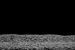 A Dusty Gravel Ridge, Showing a Blurred Foreground with Selective Focus to the Top Edge of the Small Aggregate on a Black Background.