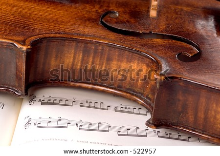 A dusty old violin rests sideways across a musical score. Only one line of the music is in focus.