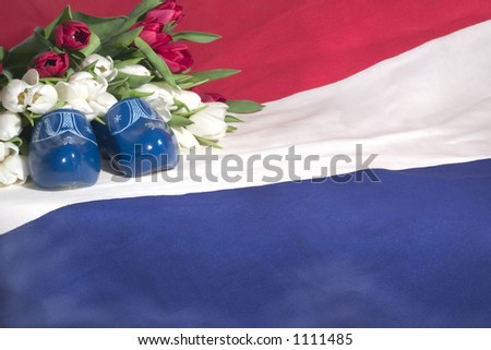 A dutch flag, red & white tulips and blue wooden shoes.