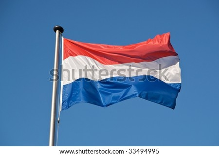 A Dutch flag with a blue sky in the background.