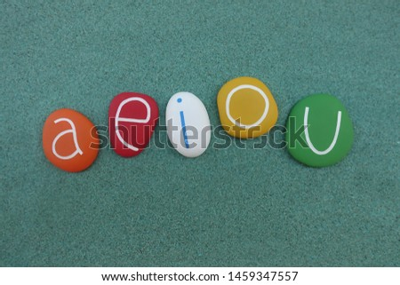 a,e,i,o,u vowel letters composed with colored stones over green sand