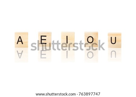 A E I O U vowel word with reflection on wooden blocks on white isolated background.